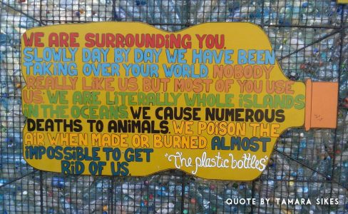 """Image: Painted text saying, """"We are surrounding you. Slowly, day by day, we have been taking over your world. Nobody really like us, but most of you use us. WE are literally whole islands in the oceans. We cause numerous deaths to animals. We poison the air when made or burned. Almost impossible to get rid of us -- the plastic bottles"""""""