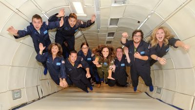 Image: A team of 10 people taking the superman pose, in zero gravity airplane