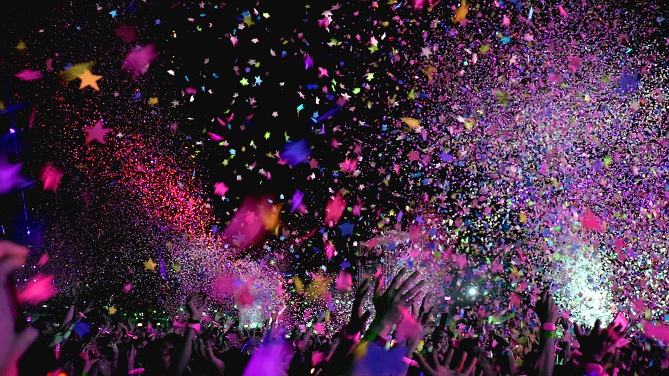 Image: Hands from a crowd reaching into the air and confetti falling into them at a concert