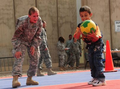 Image: Soldier plays soccer with small child