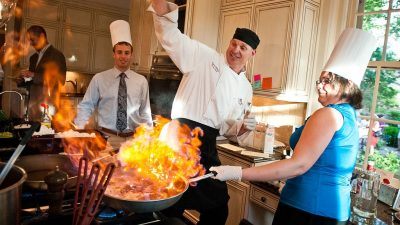 Image: People having fun cooking with flames shooting up from a large skillet