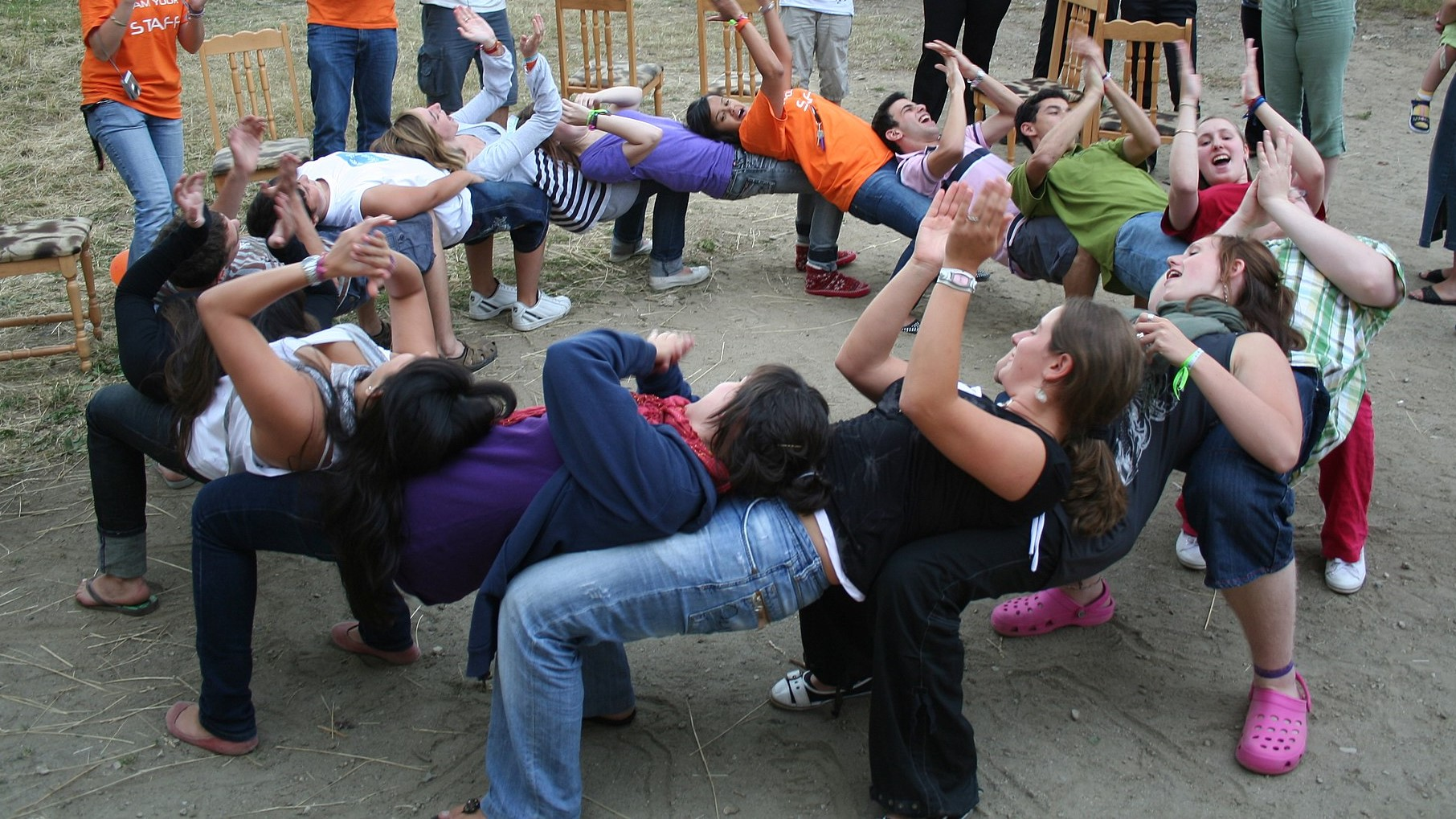 Image: A dozen people form a circle forming a human chain by balancing on each other's laps in a trust game