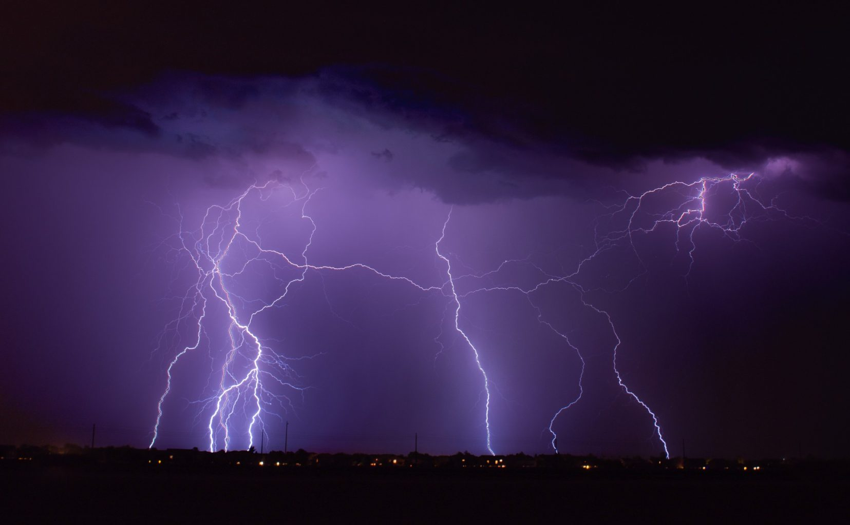 Image: Lightning rains down from a purple sky in the desert