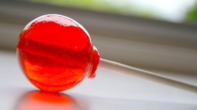 Image: A red lollipop lays on a counter-top reflecting light