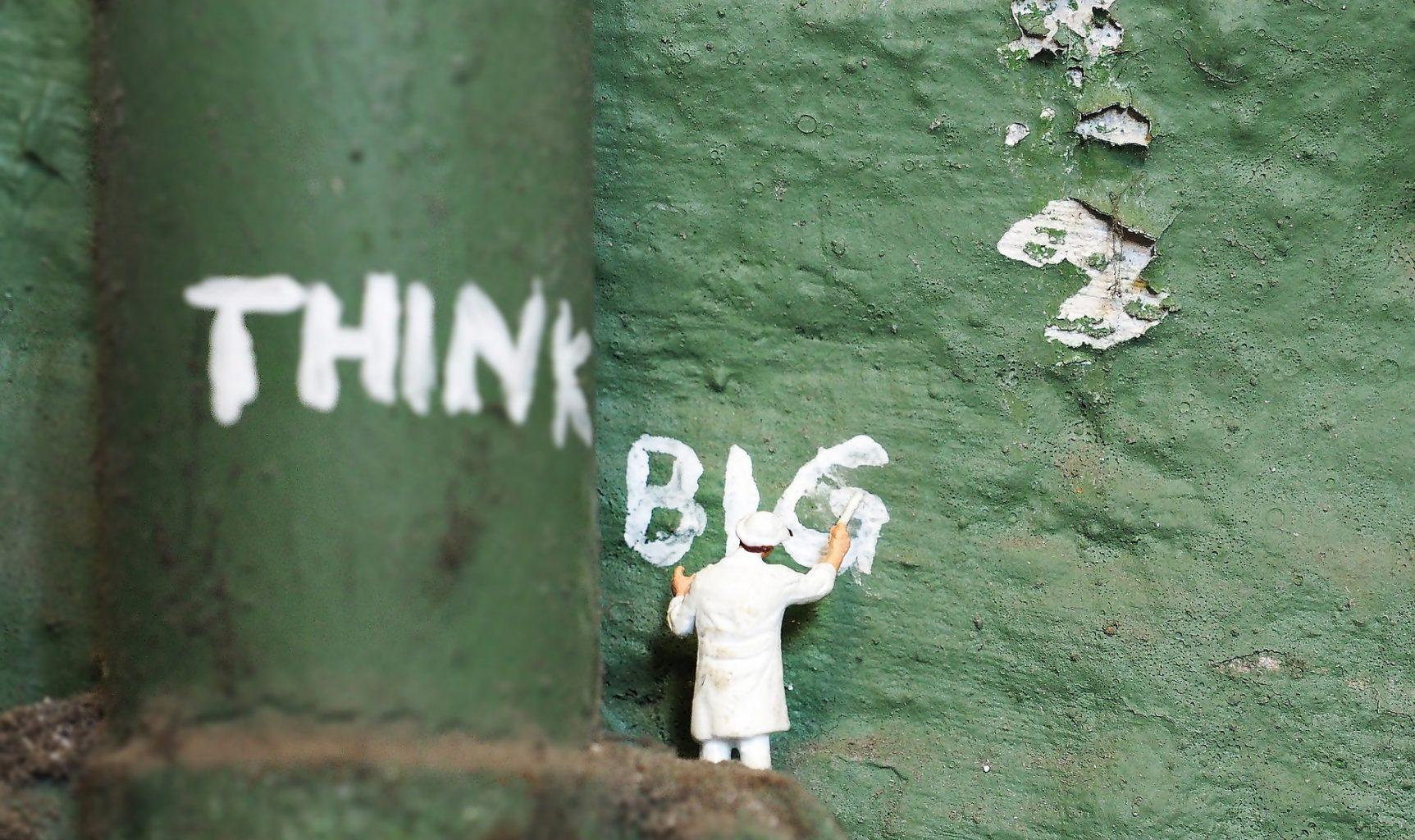 Image: Tiny figure writing think big on green wall