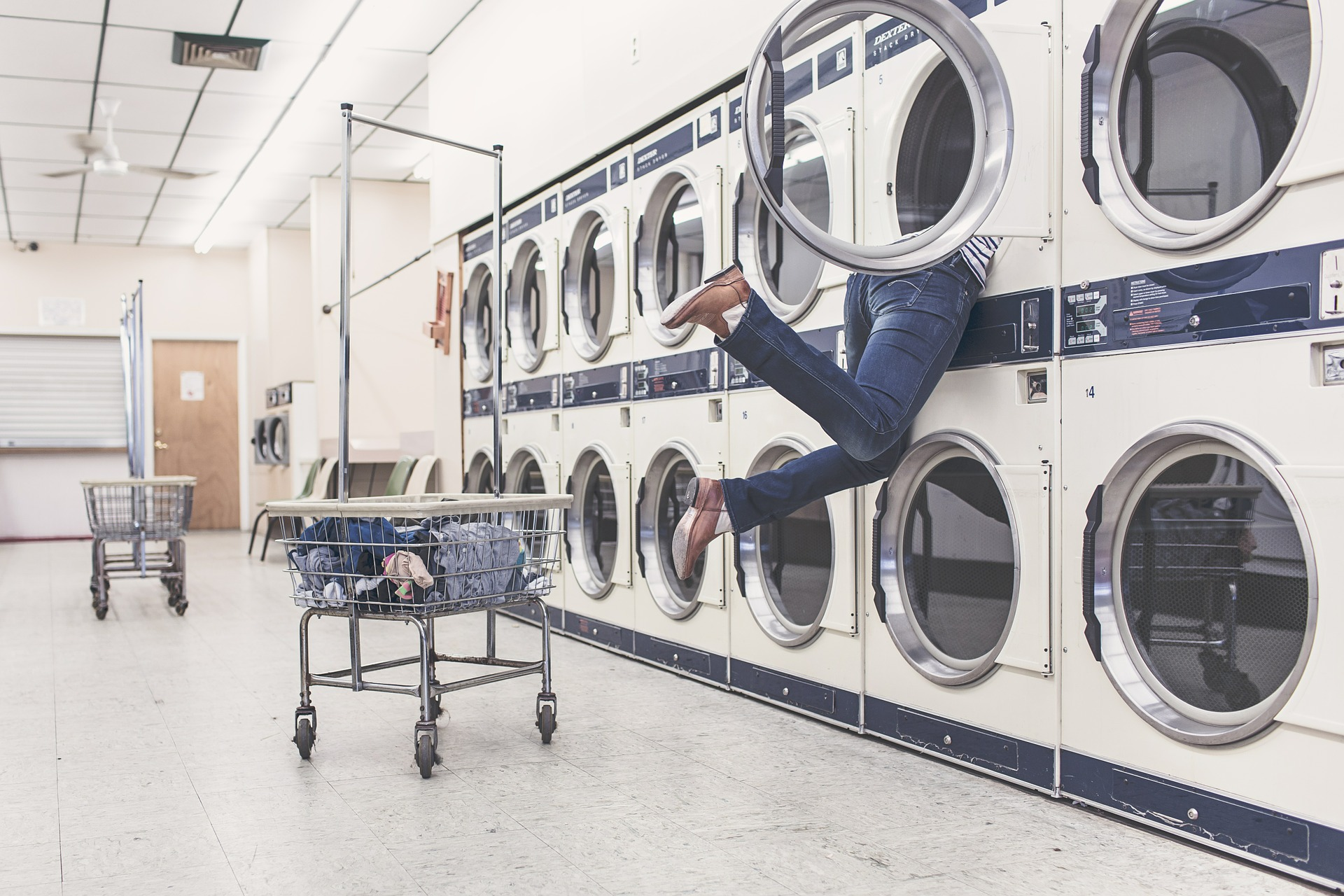 Image: Woman reaching into the back of a washing machine--an advanced technology that has changed our lives since it's inception.