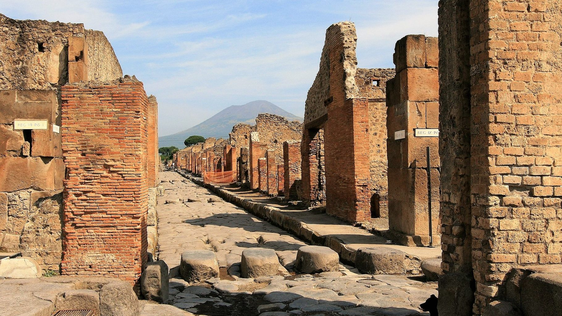 Image: Cobbled stone streets of Pompeii with Mt. Vesuvius in the distance