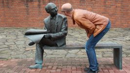 Image: Man pretending to talk to a sculpture of an old man sitting on a bench reading the newspaper
