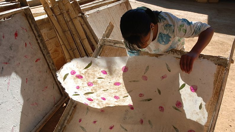 Image: Woman pulling her hand made paper off of a screen