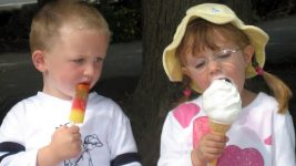 Image: Two children eating ice cream and a Popsicle. One wanting the other's treat.