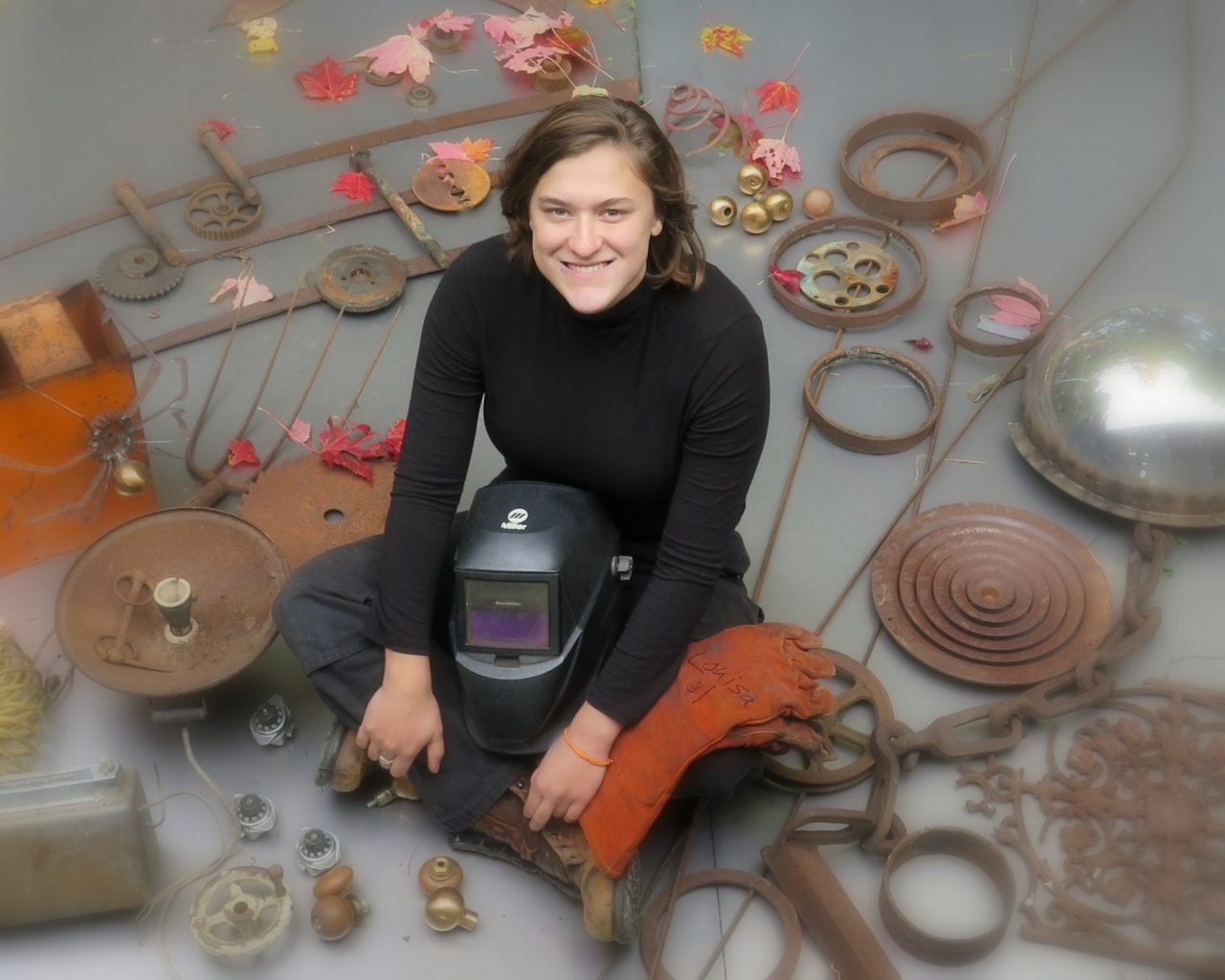 Image: Louisa sitting in the middle of rusted metal