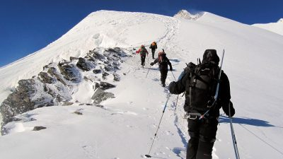 Image: Team of climbers in winter gear climbing a snowy mountain
