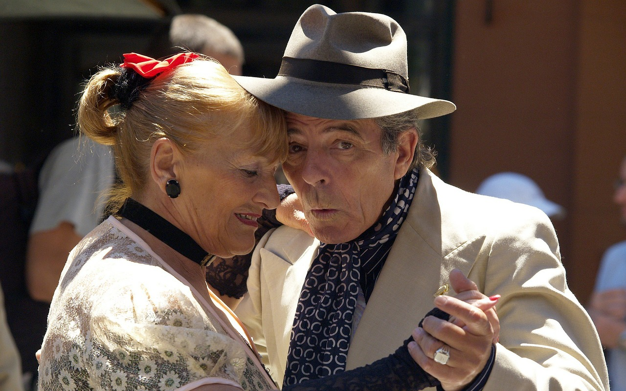 Image: Older couple dancing together. One is wearing a very nice hat.