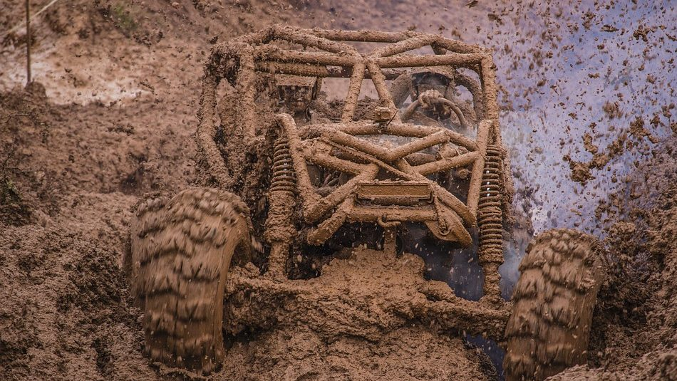 Image: A vehicle smashing through a pit of mud, a.k.a., mudding.