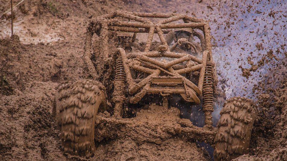 Image: A vehicle smashing through a pit of mud, a.k.a., mudding.