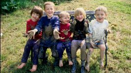 Image: 5 small children smiling, covered in mud, sitting on a bench
