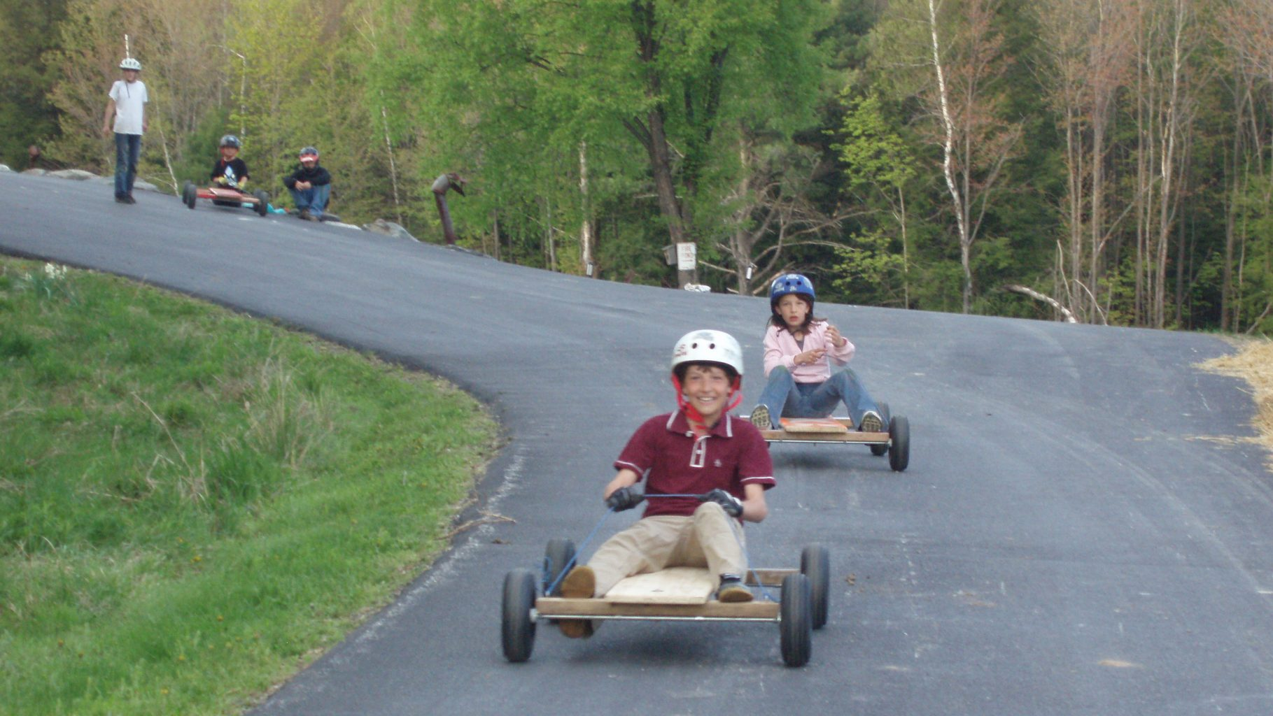 Image: Kids laughing wildly while riding home-made go-carts