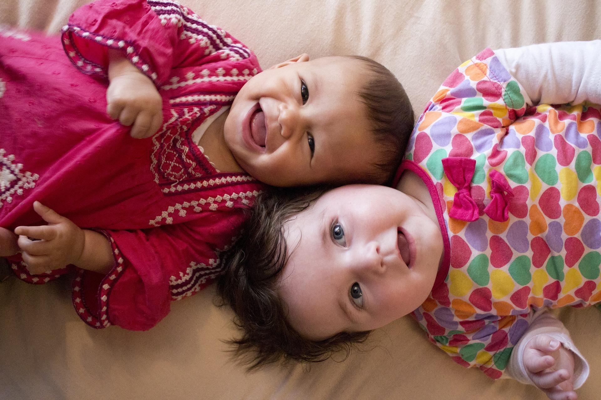 Image: Two babies talking and smiling at camera
