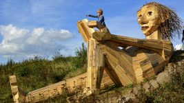 Image: A huge sculpture of a troll, 50 feet long, made of scrap wood.