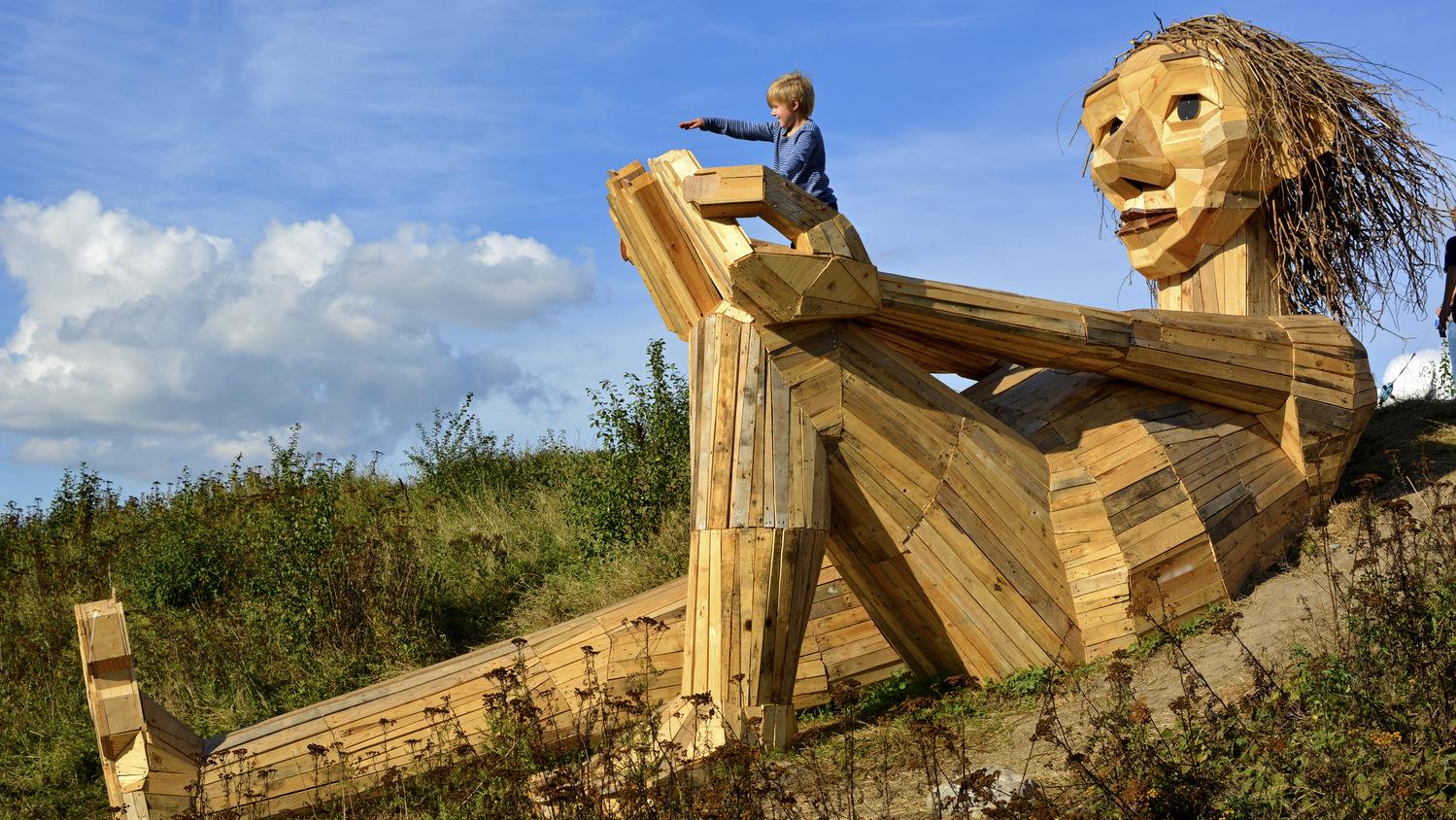 Image: A huge sculpture of a troll, 50 feet long, made of scrap wood.