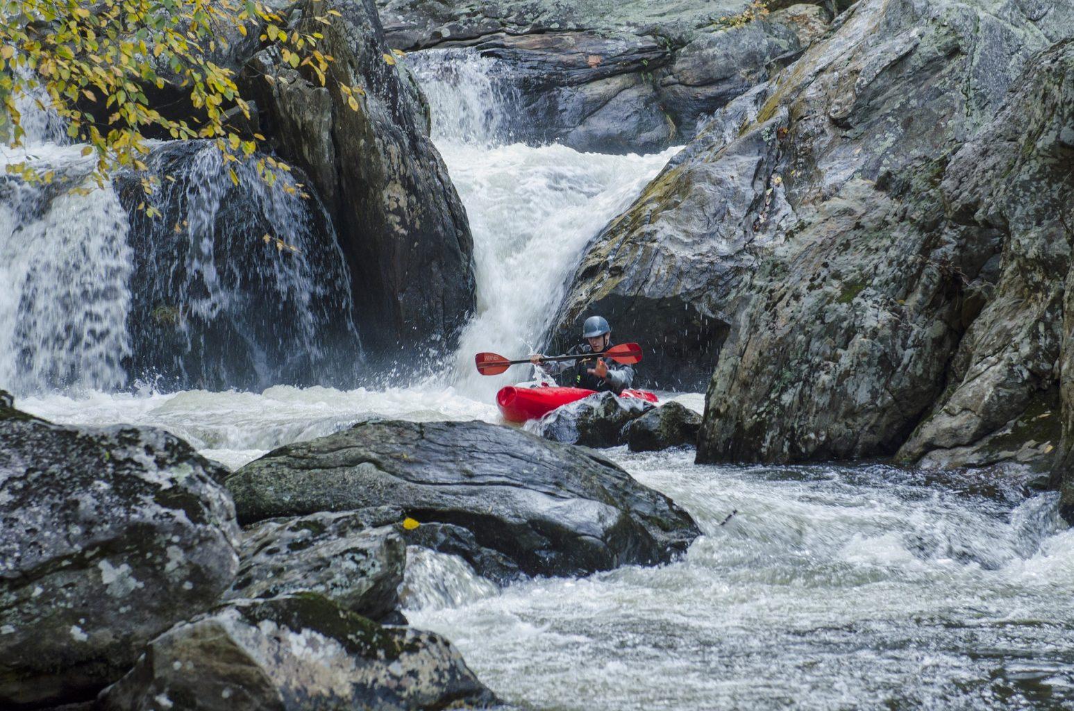Image: Person kayaking through some rocks