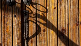 Image: Shadow of a hand reaching towards a door handle