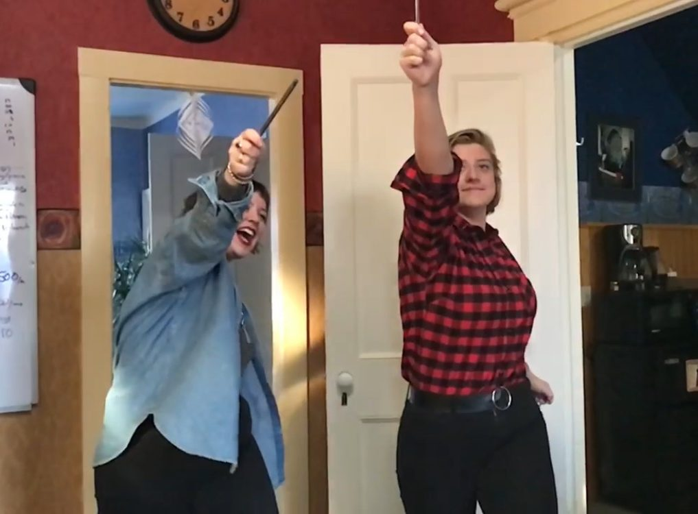 Image: Sam and Liesl waving reusable straws in the air like wands