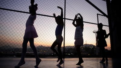 Image: Four young ballerinas lined up and practicing next to a chain mail fence.