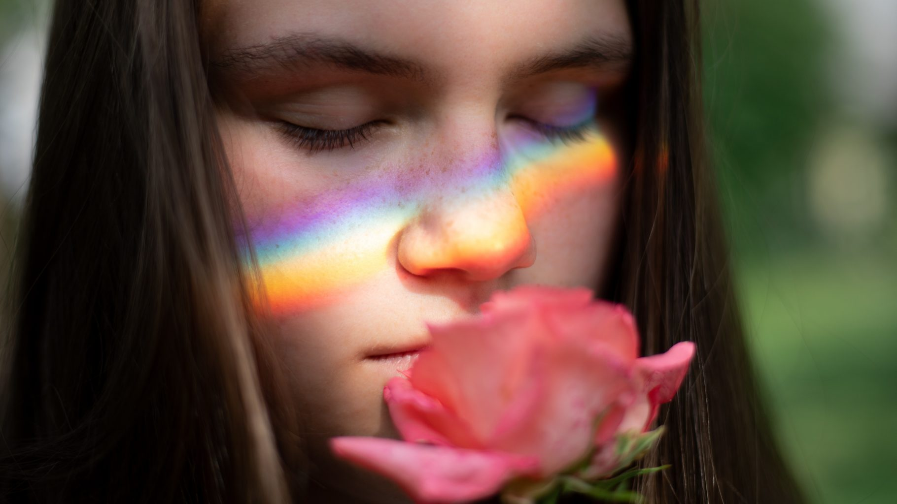 Image: A girl smelling a rose with deep satisfaction