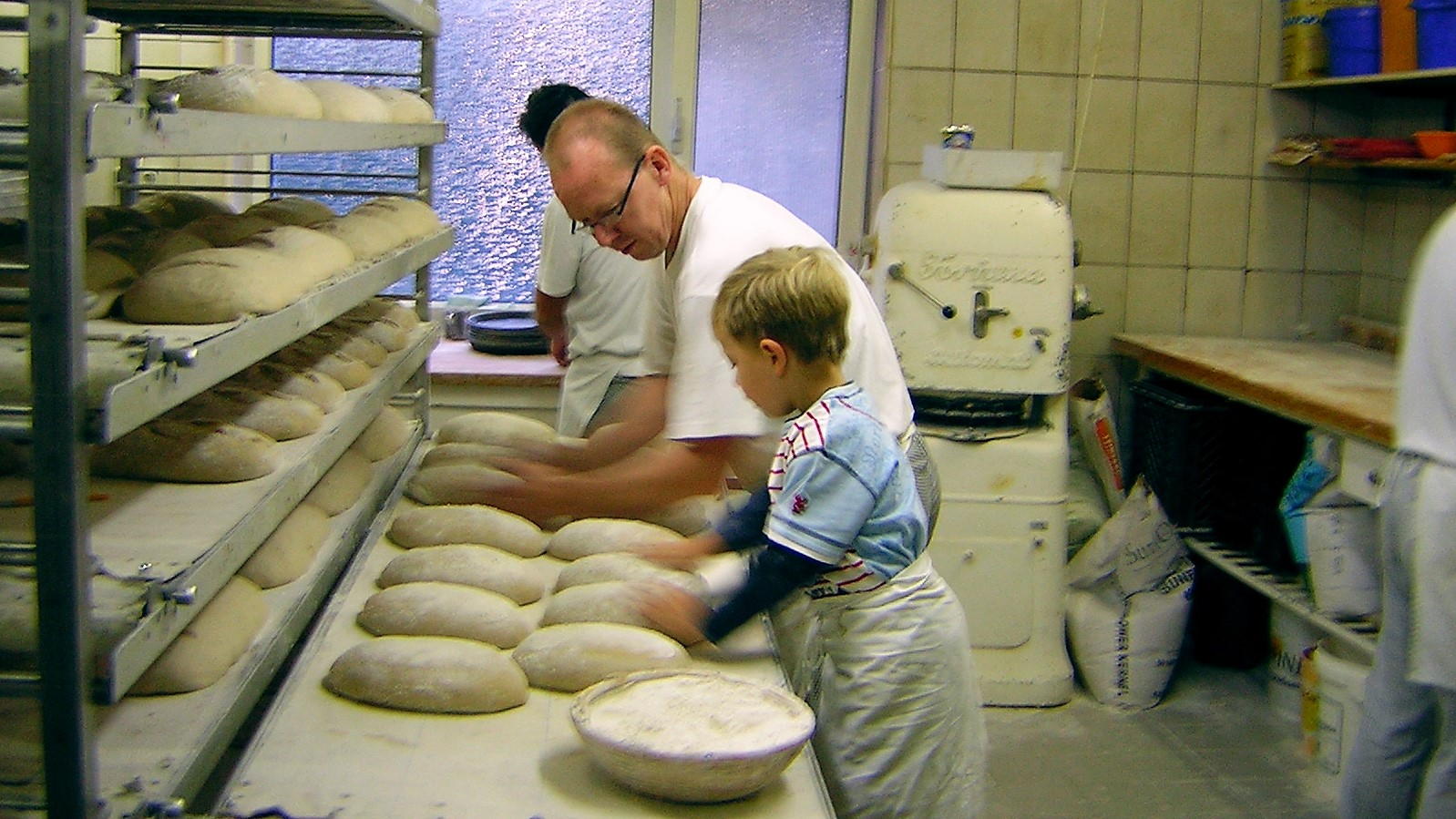 Image: man teaches a child to bake bread