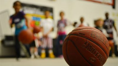 Image: A basketball close up with children in the background