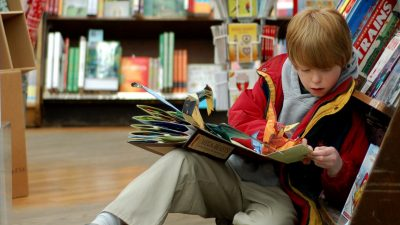 Image: a child looks deeply at a huge pop up book