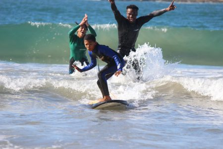 Image: A young person surfing on a small wave with two people cheering for them in the background