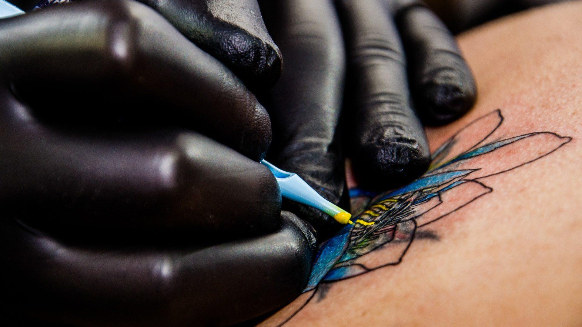 Image: Tattoo artist tattooing a flower