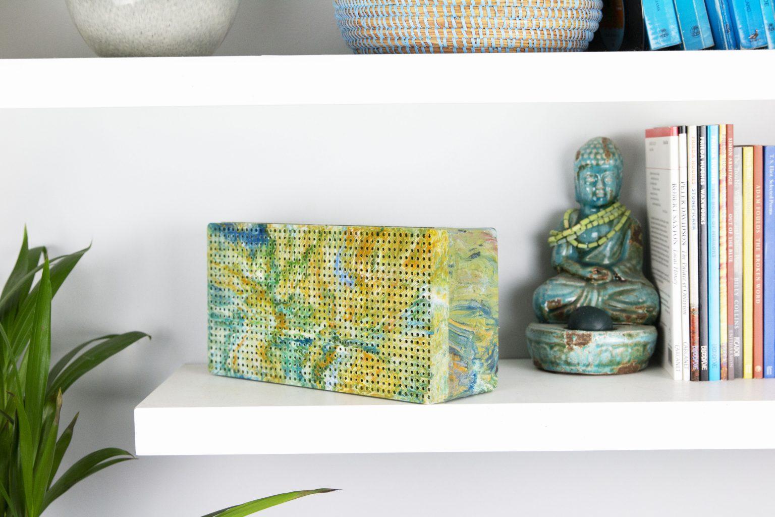 Image: Gomi Designs speaker in bright multicolors on a bookshelf