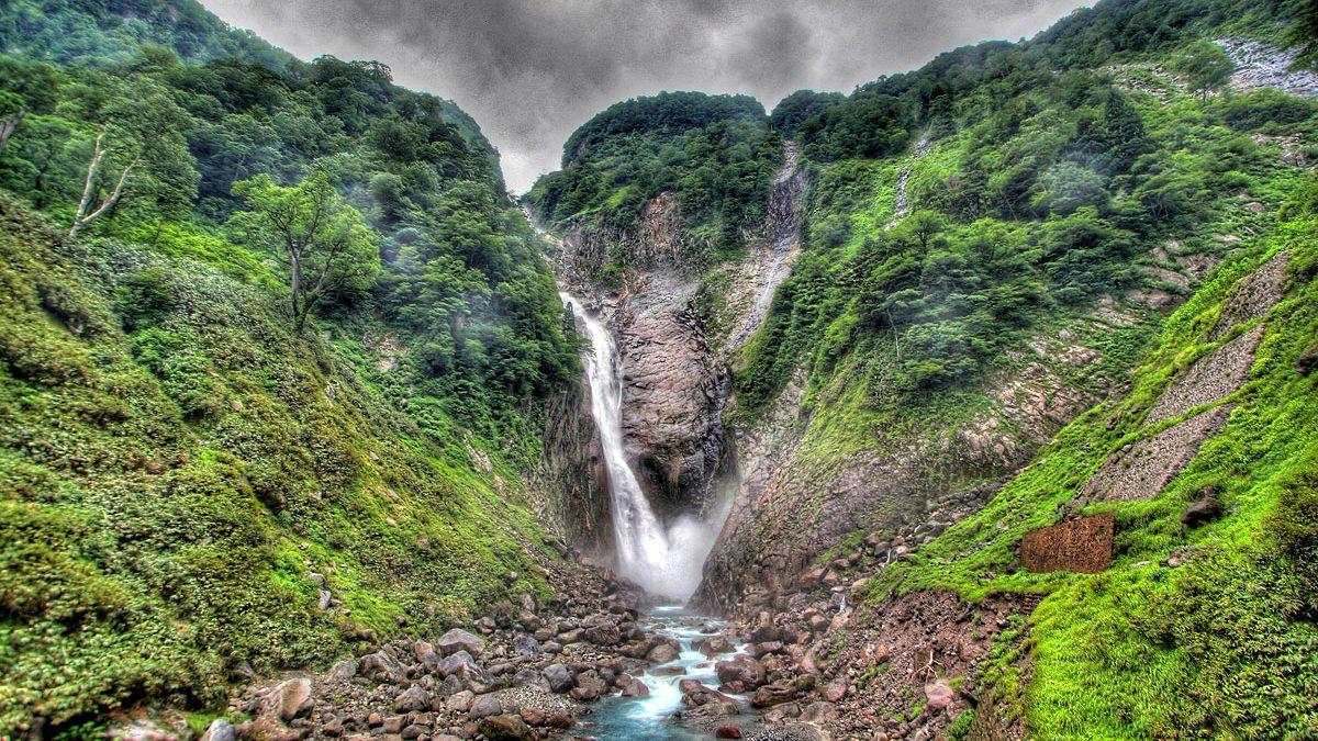 Image: Shomyo Falls a Large waterfall in Japan running between two green mountains