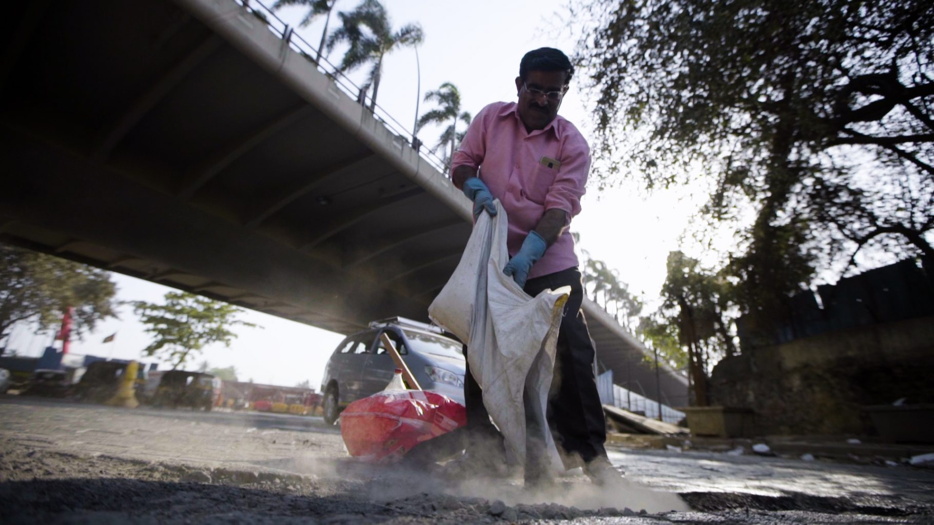 Image: man holding bag, pouring in contents to fill pothole in busy road