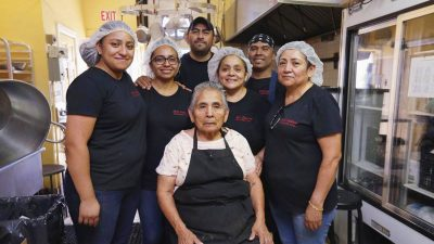 Image: the Mole Poblano Asuncion family team together in their kitchen