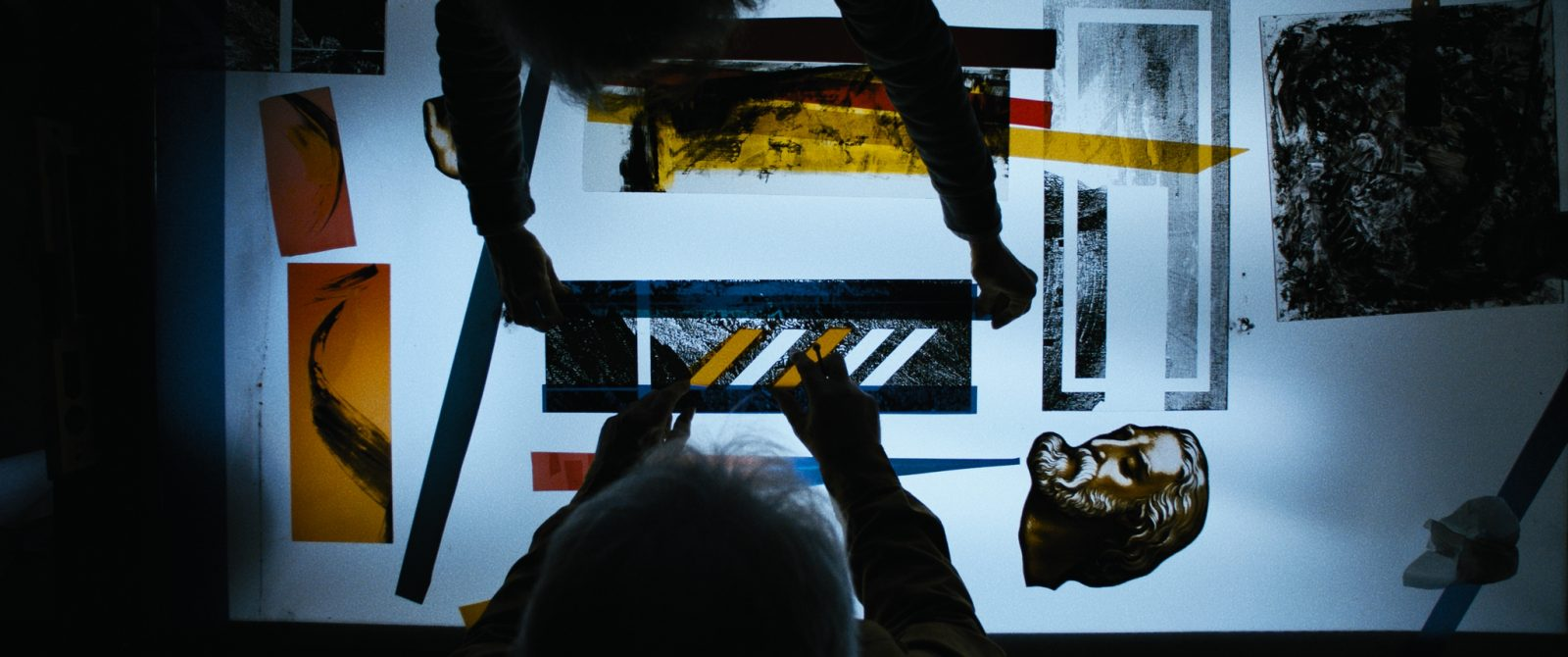 Image: people working with stained glass over a light table
