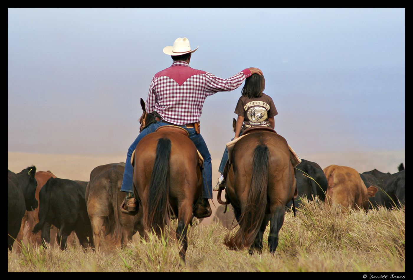 Image: Cowboy puts his hand on a child's head as they ride horses next to each other