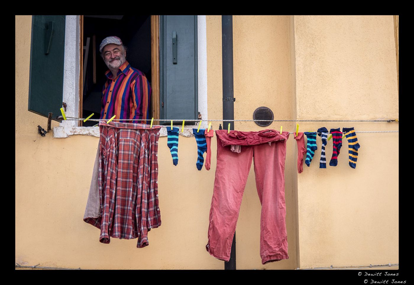 Image: Man smiles out of an open window with laundry hanging on the line in front of him