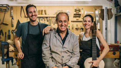Image: Luthiers team having fun while posing in their family business. Looking at camera