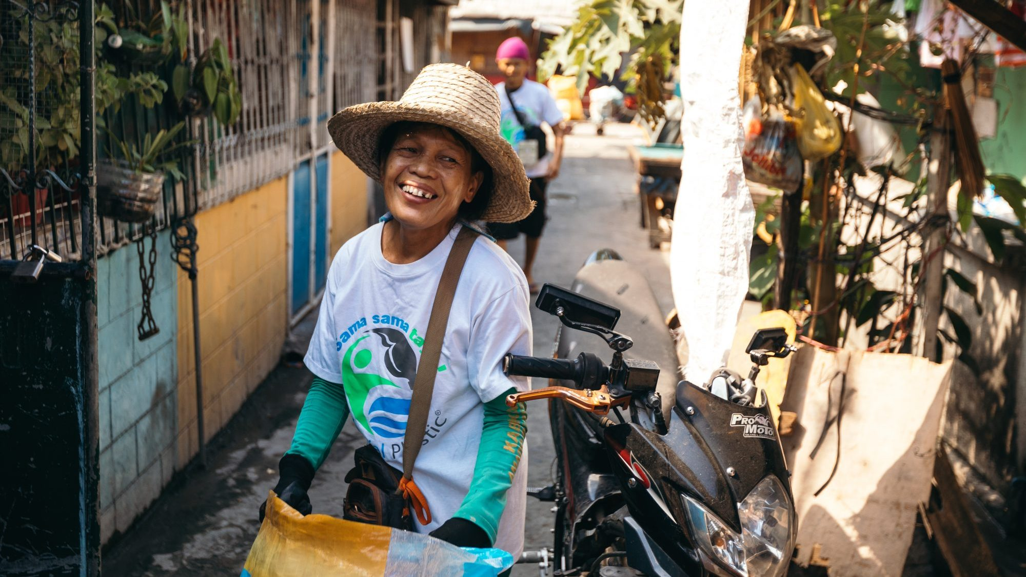 Image: Woman carrying bags of plastic in the Philippines and smiling