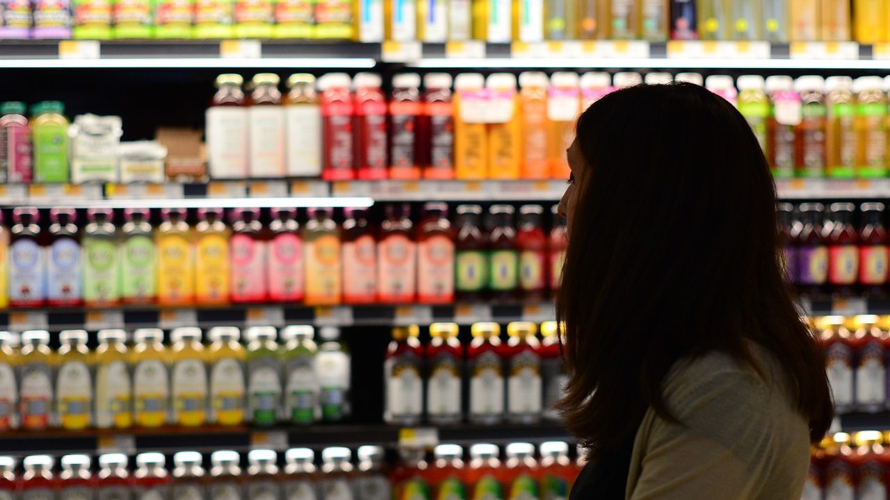 Image: Person grocery shopping. They're next to a wall of bottles.