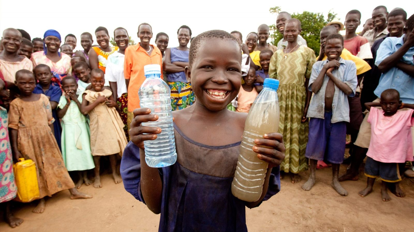 Image: child holds two water bottles one with clean healthy drinking water the other with brown muddy water, behind him are a crowd of people