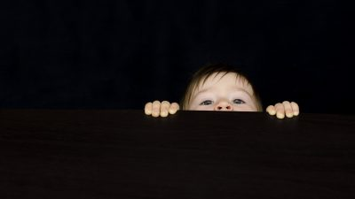 Image: A little boy peeking over a black wall, only eyes, nose and hands showing.