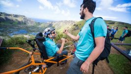 Image: Person in a trekking wheelchair fist bumping a friend atop a mountain