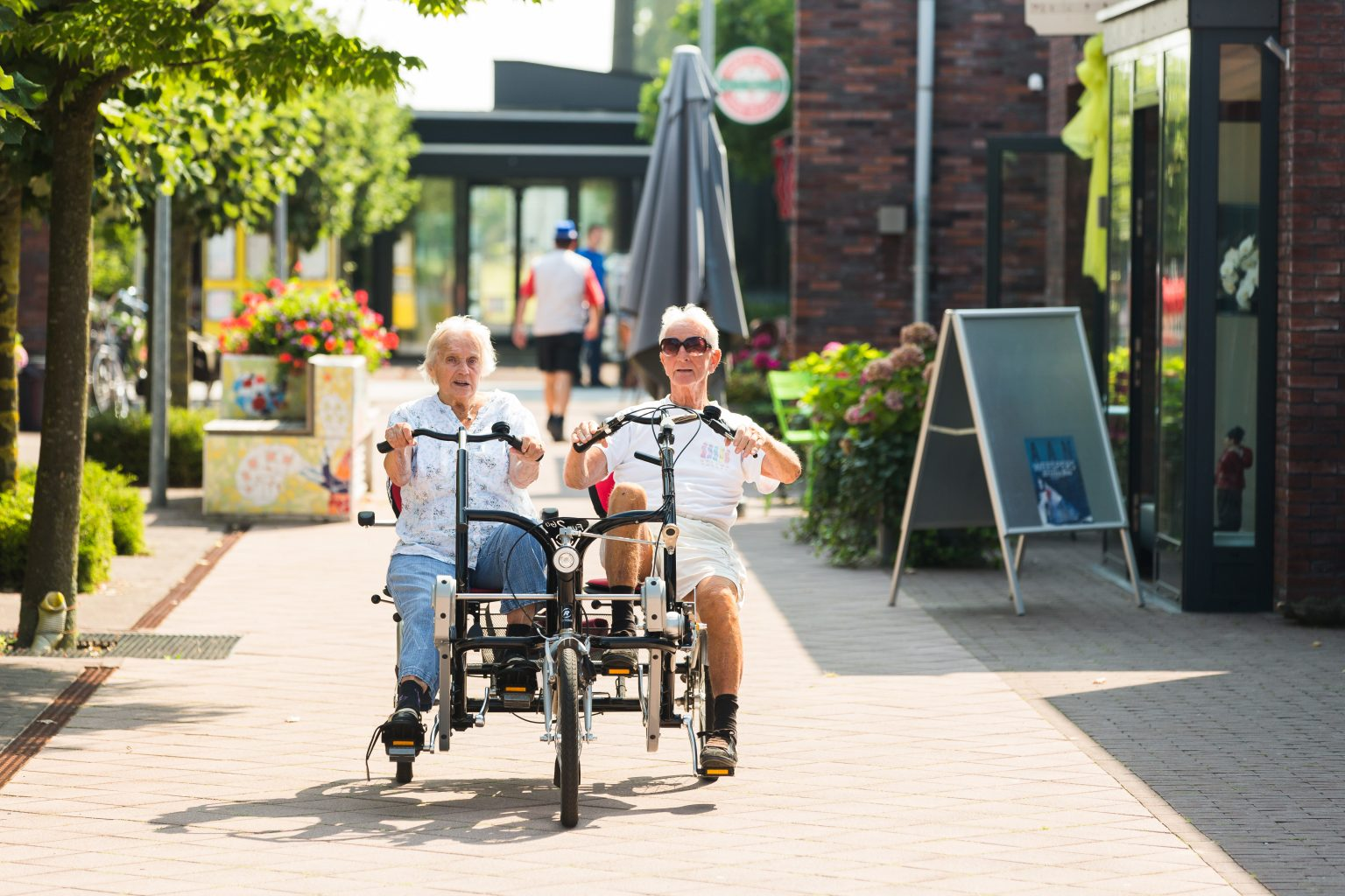 Image: Two residents of Hogeweyk cycling together outside!