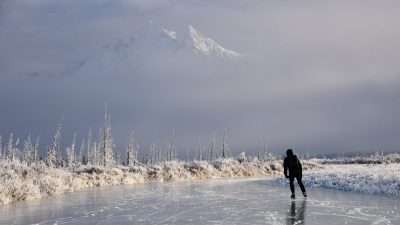 Image: lone ice skater skating in the wilderness with a mountain in the background