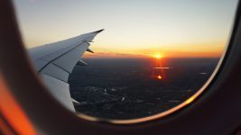 Image: Image taken from inside a plane of a plane wing with a sunset behind it